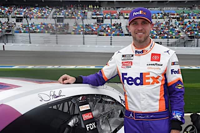 Denny Hamlin poses with his car, smiling, at Daytona 500 Photo NKP