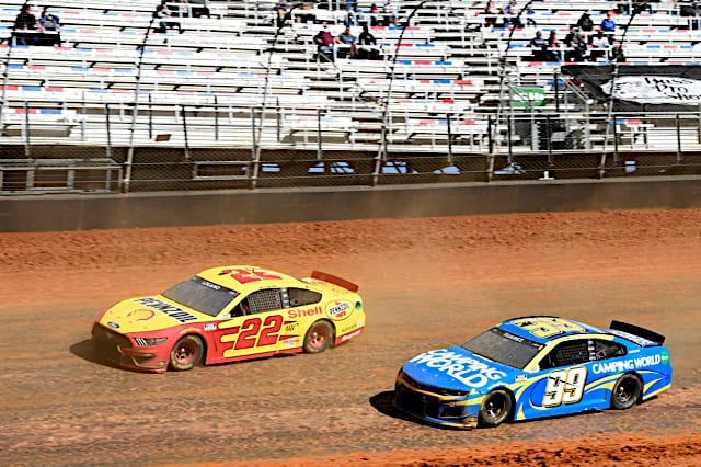 Joey Logano and Daniel Suarez race on Bristol Motor Speedway's dirt surface March 2021. (Credit: NKP)